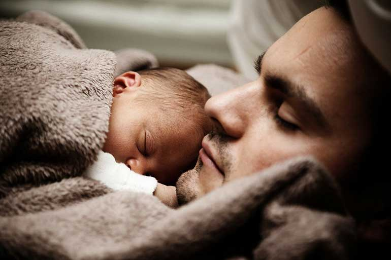 a father and his newborn is having deep sleep